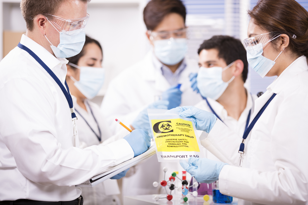 Multi-ethnic group of scientists working inside a research laboratory. Test tubes, beakers, microscope, chart. They are conducting genetic science experiments for cancer research. They hold a chemotherapy drug in a yellow bag. Molecular structure on table.