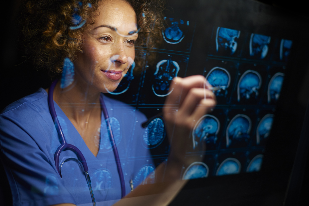 a female doctor or surgeon is analysing the digitally generated scans of a human brain